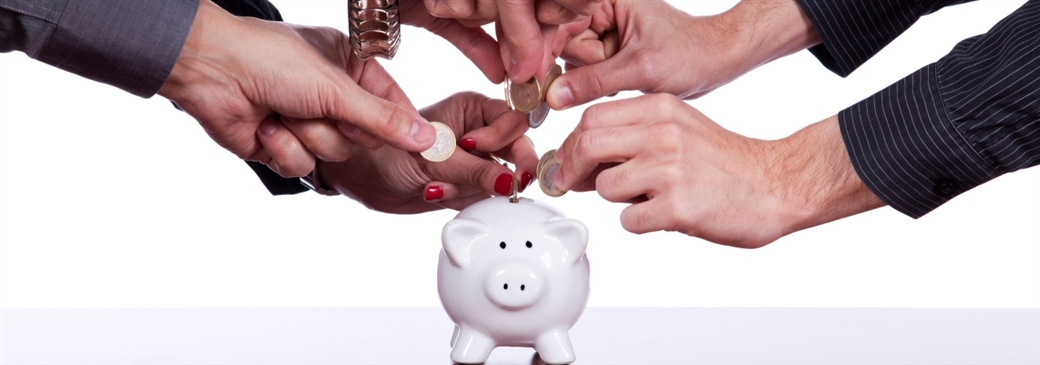 many hands placing coins into piggy bank